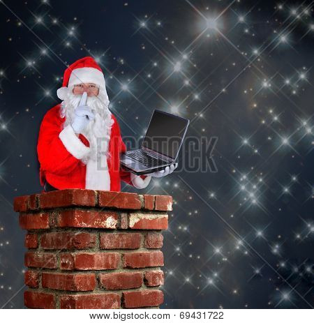 Santa Claus partially inside a chimney with a laptop and making the shh sign with a finger to his lips on a starry night background.