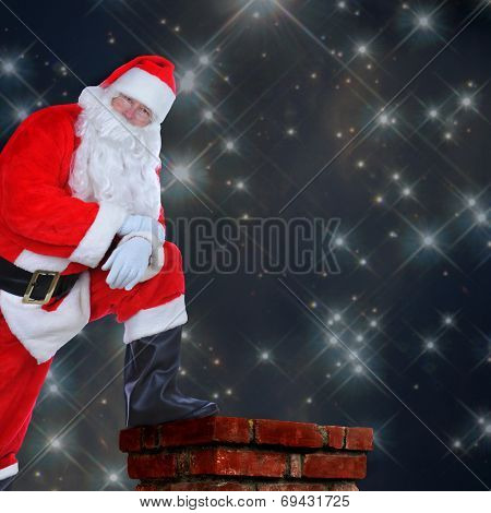 Santa Claus standing on a roof with one foot on the chimney. His arms are folded and he is leaning on his knee against a starry night background with copy space.