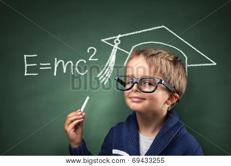 Child holding piece of chalk with E=mc2 and mortar board drawing on blackboard concept for genius student, university education and future aspirations