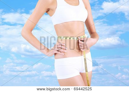 Slim girl with tape on sky background