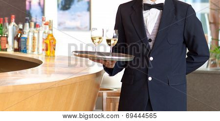 waiter holding a tray with white wine glasses