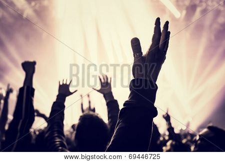 Grunge style photo of silhouette of people hands raised up on musical concert, enjoying music, dance club, active night life concept