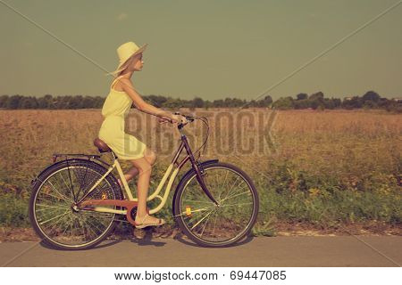 Young girl riding a retro style bike in the countryside.