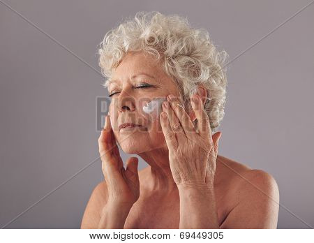 Senior Woman Applying Anti-aging Cream On Her Face