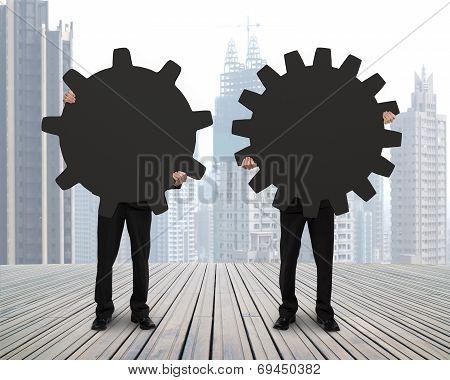 Holding Two Gears To Connect On Wooden Floor