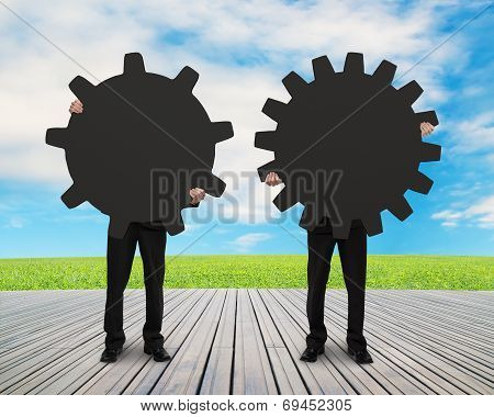 Holding Two Gears For Connecting On Wooden Floor