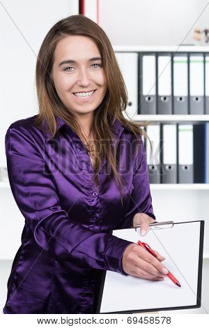 Woman Is Pointing To A Clipboard With A Pen