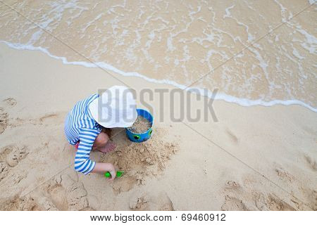 Above view of little girl wearing rash guard for sun protection playing at beach during summer vacation