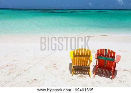 Colorful adirondack yellow and orange lounge chairs at tropical beach in Caribbean with beautiful turquoise ocean water, white sand and blue sky