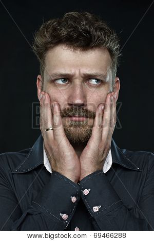 Worried married handsome bearded man anxiously press his palm to face  close up portrait