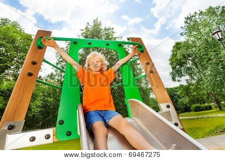 Boy slides on playground chute with hands up