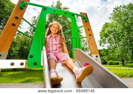 Pretty small girl on chute sitting and smiling