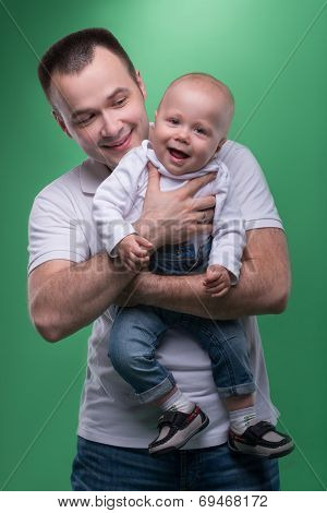 Happy smiling father embracing his baby boy