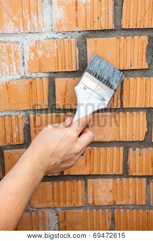 Human Hand Starting To Paint Brick Wall