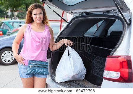 Woman Shopper Loading Bag In Trunk Of Her Car On Parking