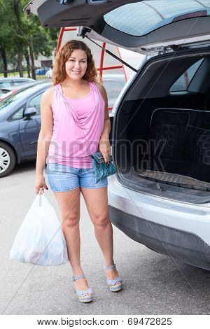 Pretty Woman With White Shopping Bag On Parking