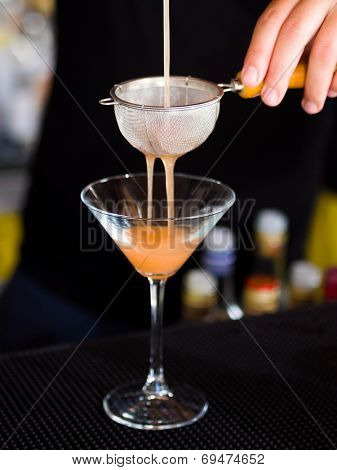Bartender pooring the cocktail into Martini glass