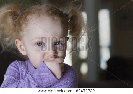 Portrait Of Cute Girl With Hand On Mouth At Home