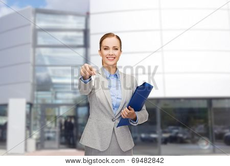 business, real estate, property and office concept - smiling businesswoman with folder and keys
