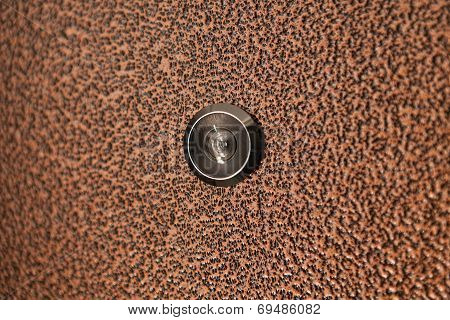 Black peephole in  brown iron door