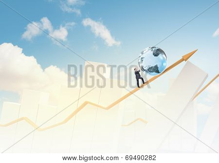 Businessman rolling Earth planet up the increasing graph