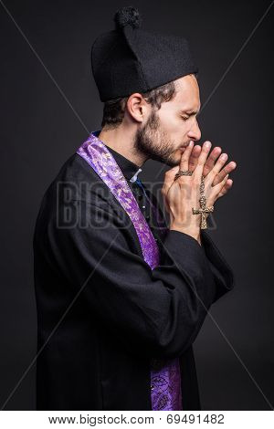 Young catholic priest praying
