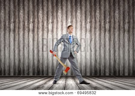 Young determined businessman with axe in hands
