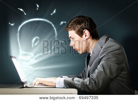 Young businessman looking shocked into laptop monitor