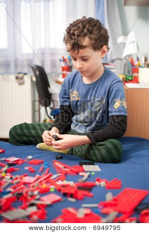 Cute Kid Playing With Plastic Blocks