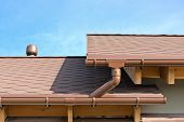 picture of red roof  - House roof detail with gutters and drainpipes