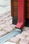 stock photo of downspouts  - Newly installed red metal downspout with lattice - JPG