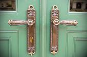 stock photo of door-handle  - Close up of antique door handles on green doors - JPG