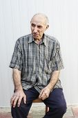 Serious Elderly Man Sitting On Chair
