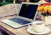 foto of hot coffee  - a cup of coffee and laptop on wood floor with flower vintage style - JPG
