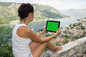 stock photo of gril  - Gril with tablet computer with green screen is sitting on the wall above sea - JPG