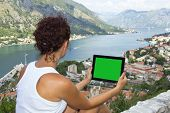 foto of gril  - Gril with tablet computer with green screen is sitting on the wall above sea - JPG