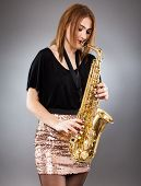 foto of saxophone player  - Beautiful blond woman saxophone player studio closeup shot - JPG