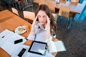 image of canteen  - Girl studying hard at the University canteen - JPG