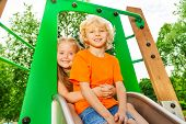 pic of chute  - Boy and girl behind hug on chute with smile on playground in summer - JPG