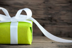 picture of ribbon decoration  - Green Present on Wood with White Ribbon and Copy Space - JPG