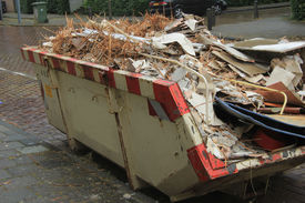 image of dumpster  - Loaded dumpster near a construction site home renovation