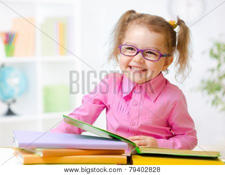 Happy child girl in glasses reading books in room