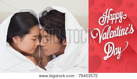 Happy couple lying on bed together under the duvet against cute valentines message