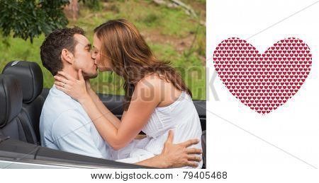 Beautiful couple kissing in back seat against valentines day pattern