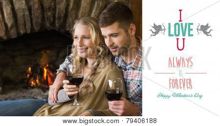 Couple with wineglasses in front of lit fireplace against cute valentines message