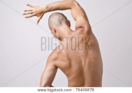 Topless man posing with his back.