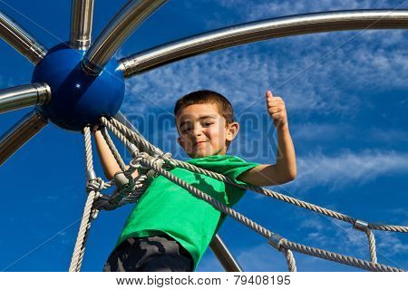 Proud Little Boy Climbs The Play Structure At The Playground