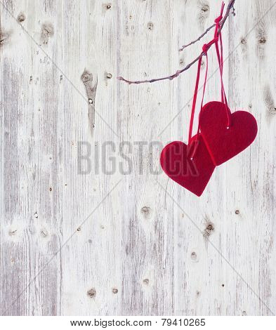 two red hearts, hanging on a branch over the old wooden background.