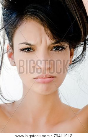 Close up on girl frowning, looking unhappy and stressed.