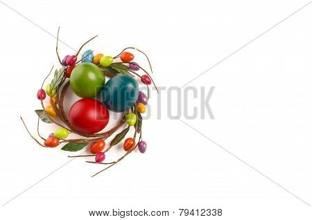 Colorful Easter eggs with circle Easter egg nest decoration around them.
